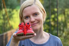 Woman holding in one extended arm small red baby shoes royalty free stock photos