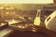 A girl in a sports suit holds a huge piece of pizza and bottle of mojito on the sunset city background. A girl with a beautiful breast in a sports suit holds a stock photos