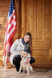 Girl with beautiful dog in front of mountain cottage Royalty Free Stock Photos