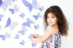 The girl against a wall decorated with butterfly Royalty Free Stock Photography