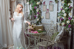 The girl in a beautiful dress among the flowers. Blonde girl in a beautiful dress standing among the flowers in the room Royalty Free Stock Photography