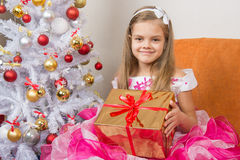 Girl in beautiful dress gave New Year gift Royalty Free Stock Photography