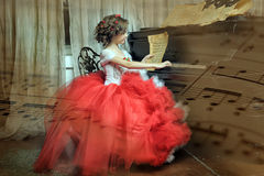 Girl in a beautiful dress sits at the piano Stock Photography