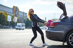 The girl takes out her pink suitcase from the trunk. The girl is beautiful, with glasses, the blonde pulls her pink suitcase out of the trunk of the car Royalty Free Stock Image