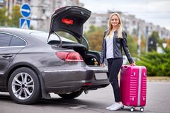 The girl takes out her pink suitcase from the trunk. The girl is beautiful, with glasses, the blonde pulls her pink suitcase out of the trunk of the car Royalty Free Stock Photo