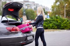The girl takes out her pink suitcase from the trunk Stock Photos