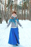 A girl with beautiful hair on her head in a Slavic style in full growth in the winter forest royalty free stock photography