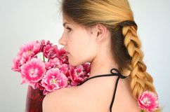 A girl with a beautiful hairdress with a bouquet of tulips is a sort of Columbus. Hair braided with four strands Royalty Free Stock Photography