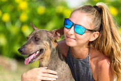 The girl beautiful in jeans shorts and an undershirt also gatsya with dogs, game with dogs on the beach. Stock Images