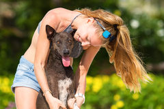 The girl beautiful in jeans shorts and an undershirt also gatsya with dogs, game with dogs on the beach. Stock Photos