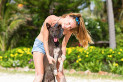 The girl beautiful in jeans shorts and an undershirt also gatsya with dogs, game with dogs on the beach. Stock Photography