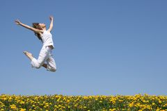 Girl in a beautiful jump. Young woman in a beautiful happy jump in flowering field Royalty Free Stock Images