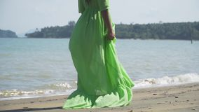 A girl in a beautiful, light, lush green dress is walking along the beach. Back view. Slow motion. Thailand stock video