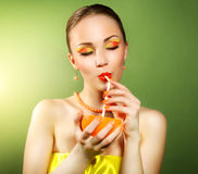 Girl with beautiful make-up holding orange fruit Stock Photography