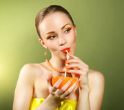Girl with beautiful make-up holding orange fruit Stock Photos
