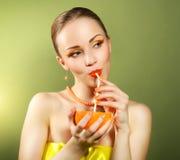 Girl with beautiful make-up holding orange fruit Stock Photos