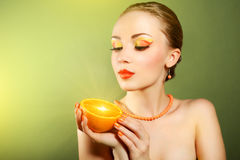 Girl with beautiful make-up holding orange fruit Stock Images
