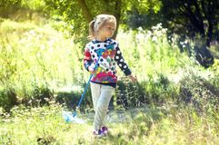Girl in the beautiful park, with a net catches butterflies, smiles and laughs, playful mood, childish pranks. Little girl in the beautiful park, with a net Stock Photography