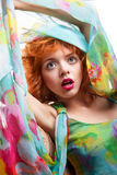Girl with red hair and colorful dress over white Stock Images