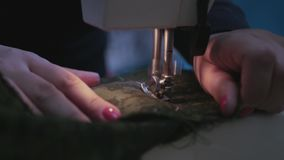 Girl with beautiful red nails on the sewing machine sews a beautiful green dress, cut with scissors thread, 3840x2160 stock video
