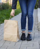 Girl in beautiful shoes leaned over a paper bag. Stock Photography