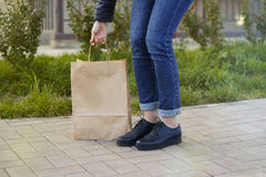Girl in beautiful shoes leaned over a paper bag. Stock Photo