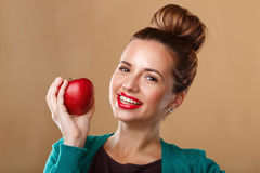 Girl with a beautiful smile holding a red apple. Stock Photo
