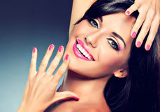 Girl with beautiful smile. Model girl with a beautiful smile and fuchsia color manicure Royalty Free Stock Photo