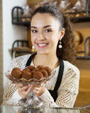 Girl with beautiful smile offering very tasty chocolate truffles Royalty Free Stock Images
