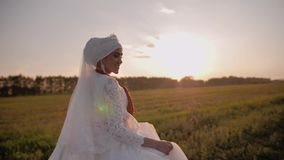 Girl in a beautiful white national dress is a beautiful meadow in the evening sun. Beautiful young girl. stock video