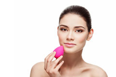 Girl with beauty blender sponge. Beautiful young woman applying makeup using beauty blender sponge. Isolated over white background stock photos