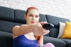 Girl With Beauty Mask Watching Television At Home. Girl with beauty mask watching televison at home. Young woman changing channel with remote control in living Royalty Free Stock Photography