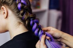 Girl in the beauty salon is weaved with braids. braided pigtails. stock images