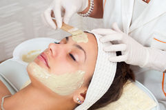 Girl in the beauty spa with facial mask Stock Image