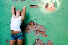 Girl becide the wall Stock Photography