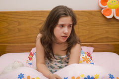 Girl in bed. A young girl in bed feeling sad Royalty Free Stock Photo