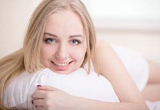 Girl In Bed. Beautiful young blonde girl lying on a bed in her bedroom Royalty Free Stock Image