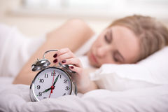 Girl In Bed. Young woman with alarmclock on the bed at the morning Stock Photography