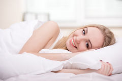Girl In Bed. Beautiful young blonde girl lying on a bed in her bedroom Stock Image