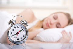 Girl In Bed. Young woman with alarmclock on the bed at the morning Stock Images
