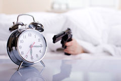 Girl In Bed. Young pretty girl holding a gun and shoots the alarm in the morning Stock Photos