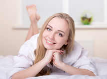 Girl In Bed. Beautiful young blonde girl lying on a bed in her bedroom Stock Photos