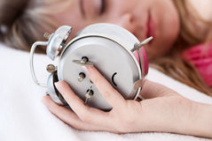 Girl in bed with alarm clock Stock Photography