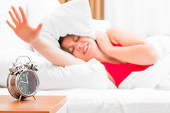 Girl in bed and alarm clock Royalty Free Stock Image
