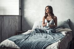 Girl in bed. Beautiful young girl is holding a cup, looking away and smiling while resting in bed at home Royalty Free Stock Images