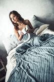Girl in bed. Beautiful young girl is holding a cup, looking away and smiling while resting in bed at home Royalty Free Stock Image