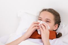 Girl in bed blows a snot from her nose into a napkin Stock Photos
