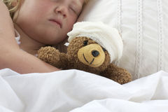 Girl in bed cuddling a teddy with bandage Royalty Free Stock Images