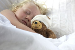 Girl in bed cuddling a teddy with bandage Royalty Free Stock Image