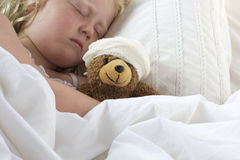 Girl in bed cuddling teddy with bandage Royalty Free Stock Photos